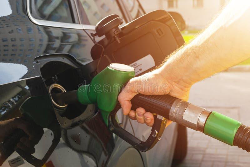 Refueling samochód przy benzynowej staci paliwową pompą Mężczyzna kierowcy ręka refilling benzynę i pompuje oliwi samochód z pali zdjęcie stock