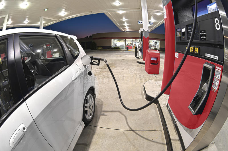 Refueling Small Economy Car At Gasoline Station Revised. A fish eye lens view of a small economy car gets a night time fill-up at a gas station stock image