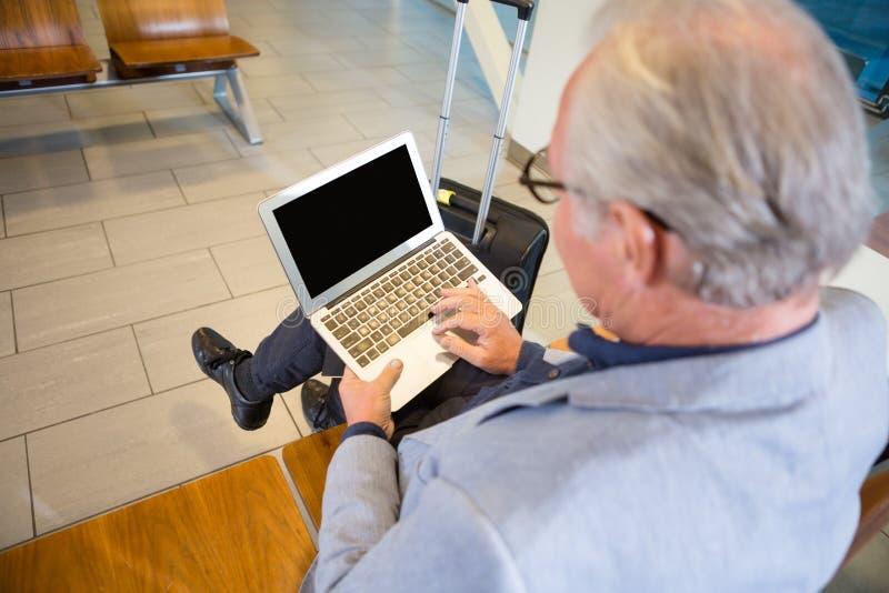 Refuge d'aéroport d'Using Laptop In d'homme d'affaires image libre de droits