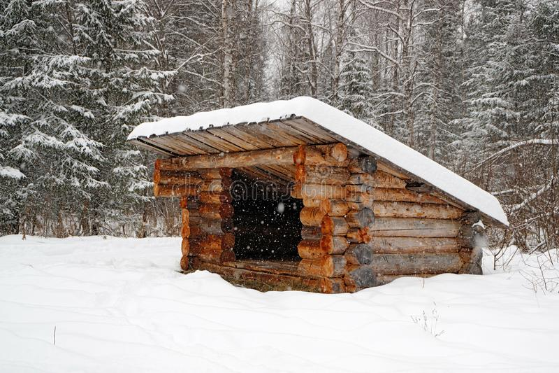 A refuge for partisans in the forest in winter, a structure of logs with a roof royalty free stock images