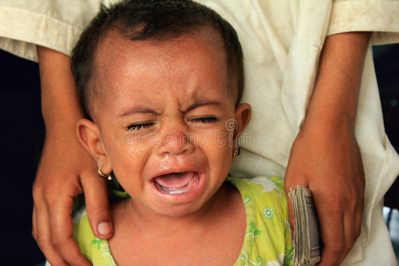 Refugee Baby Crying in Hunger. A Malnourished Refugee Baby cries in hunger at a Refugee Camp setup for Flood Victims in Shikarpur, Pakistan. The Baby is one of royalty free stock image