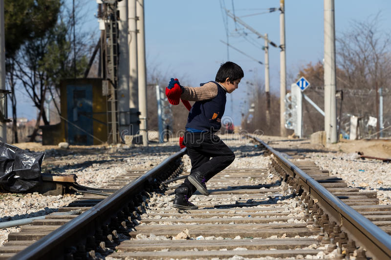 A refugee child sits on the railway near the border crossing bet. Idomeni, Greece, February 7, 2016:A refugee child sits on the railway near the border crossing stock photography
