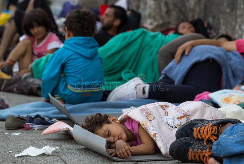 Refugee child sleeping at Keleti train station in Hungary. Refugee child sleeping on the ground. Refugees and migrants, most of them from Syria, are gathered at