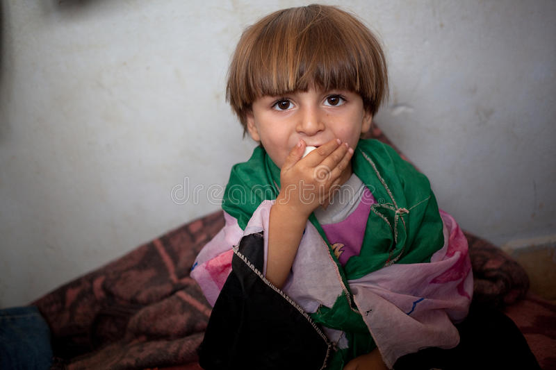 Refugee child wrapped in homemade Free Syrian flag, Atmeh, Syria. royalty free stock photo
