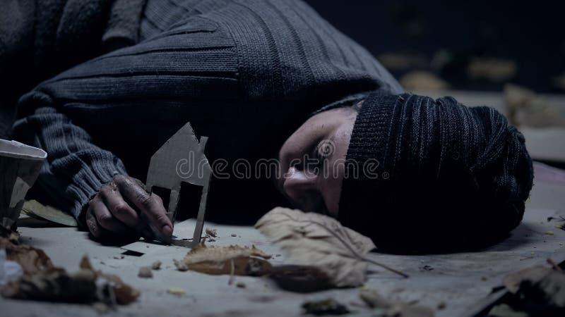 Refugiado de congelaci?n que duerme en la calle y sostener la casa del papel, hogar perdido imagen de archivo