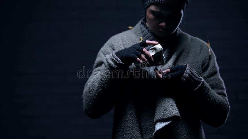 Refugiado pobre que cuenta monedas de la taza de papel, mendigo que vive en la calle, donaci?n fotos de archivo libres de regalías