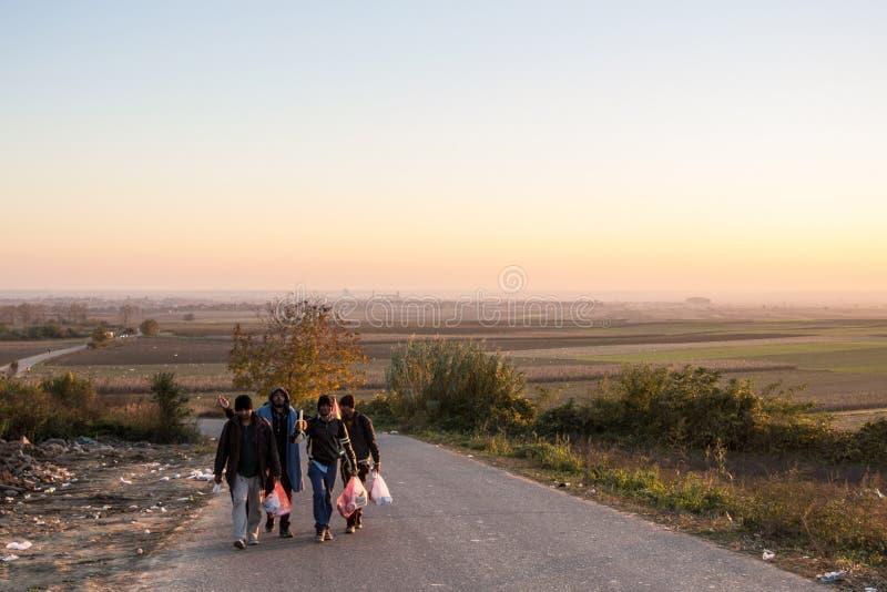 Refugiados que andam com os sacos pesados na maneira à Croácia na beira sérvio croata, na rota de Balcãs foto de stock royalty free