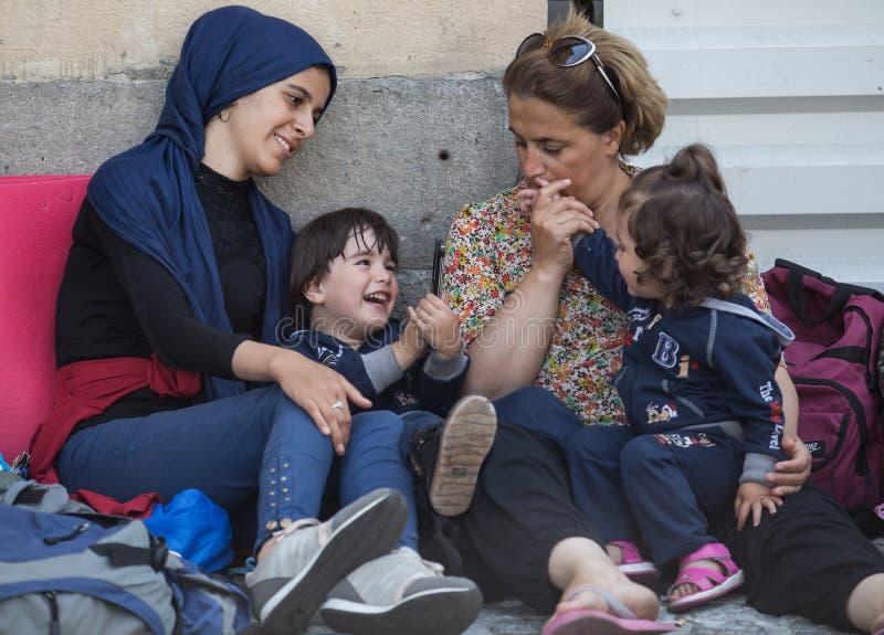 Refugiados que confortan a sus niños en la estación de tren de Keleti en Budapest fotos de archivo