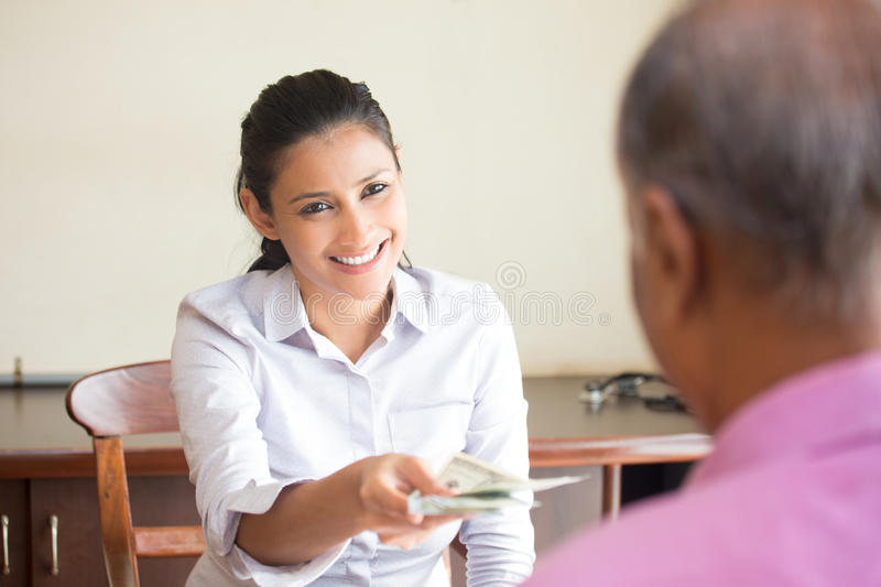 Refund time. Closeup portrait, women giving cash back refund, indoors office background. Excellent customer service with a smile royalty free stock photos
