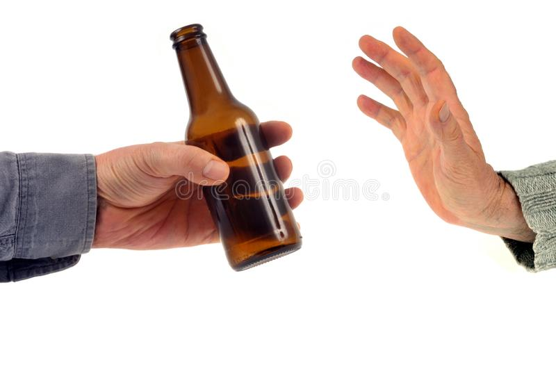 Refuse a bottle of beer on a white background. Abstinence concept by refusing bottled alcohol in close-up stock photography