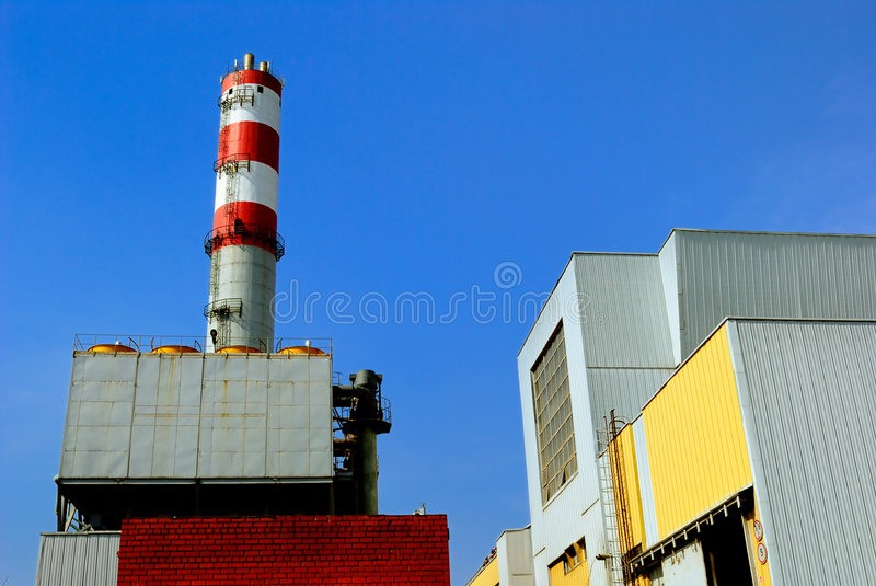 Refuse incinerator. Constructions of refuse incinerator power station over blue sky royalty free stock images