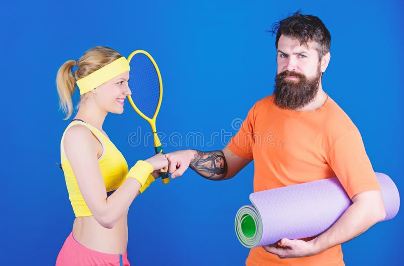 Refuse to Lose. Sporty couple training with fitness mat and tennis racket. Happy woman and bearded man workout in gym stock photo