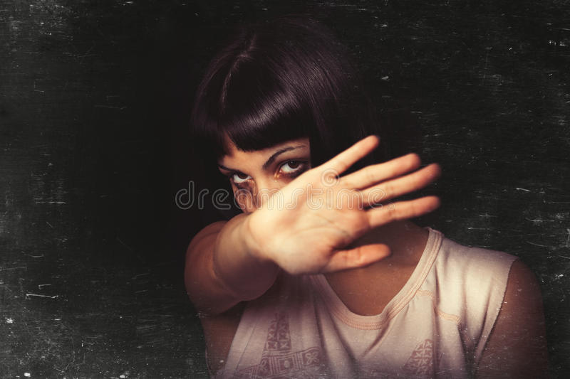 Refusing, stop violence against women. A young girl with her hand away and rejects violence of someone. Tears and crying. Black background. Focus on the face stock photography
