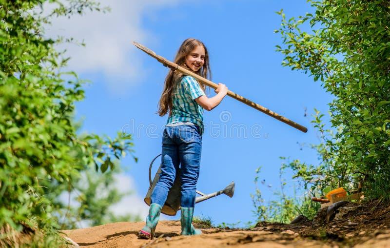 Regadera de la pala del control del ni?o de la muchacha Ayudante de la lista de control de la primavera que cultiva un huerto peq imágenes de archivo libres de regalías