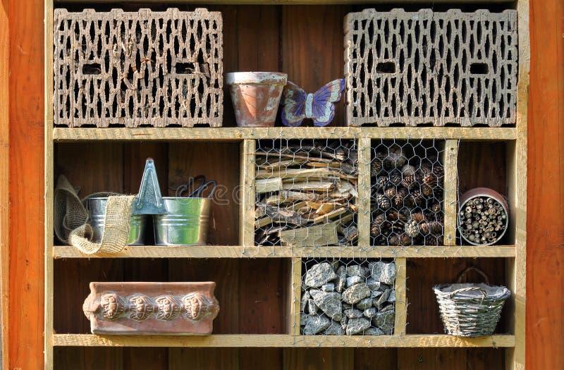Regal mit Insektenhotel- und -gartengeräten stockbild