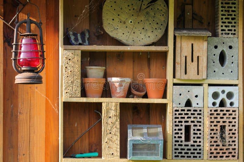 Regal mit Insektenhotel- und -gartengeräten lizenzfreies stockfoto