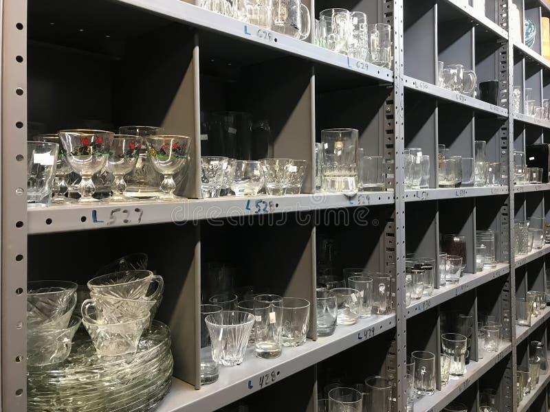 Regale von benutzten klaren Glaswarentellern im Gebrauchtwarengeschäft lizenzfreie stockfotografie