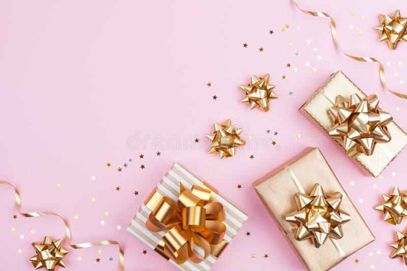 Regali di modo o scatole dei presente con gli archi dorati e coriandoli della stella sulla vista superiore del fondo pastello ros fotografia stock libera da diritti