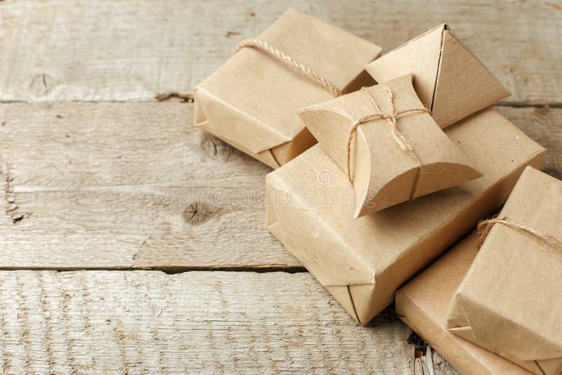 Regali di Natale avvolti in pacchetto del mestiere di carta su fondo di legno d'annata, spazio della copia regali alla moda, salu immagini stock