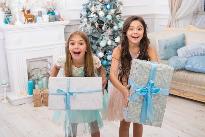 Regali di Natale di consegna ragazze dei piccoli bambini con il presente di natale Nuovo anno felice le sorelline felici celebran immagine stock libera da diritti