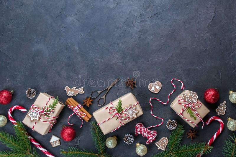 Regali di natale di Framewith del fondo di natale e bastoncino di zucchero scuri, decorazioni, pigne, rami dell'abete immagine stock