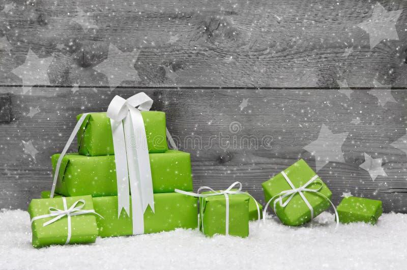 Regali di Natale verdi con neve su fondo di legno grigio per immagini stock libere da diritti