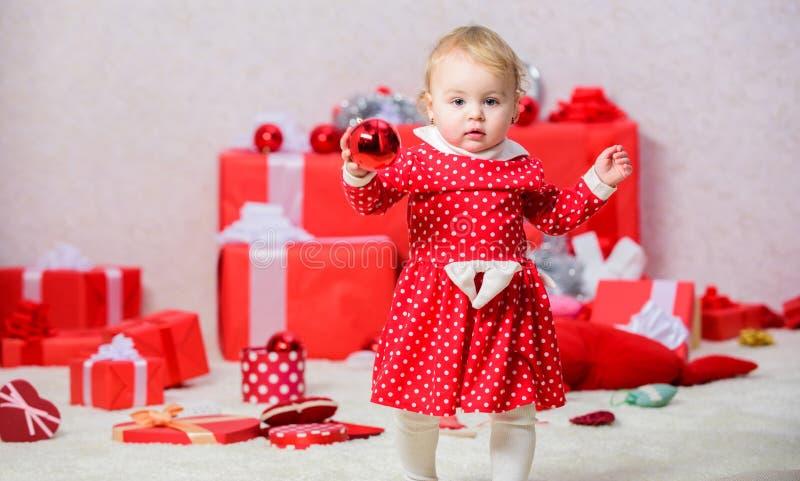Regali per primo natale del bambino Cose da fare con i bambini a natale Piccolo gioco della neonata vicino al mucchio dei conteni fotografia stock