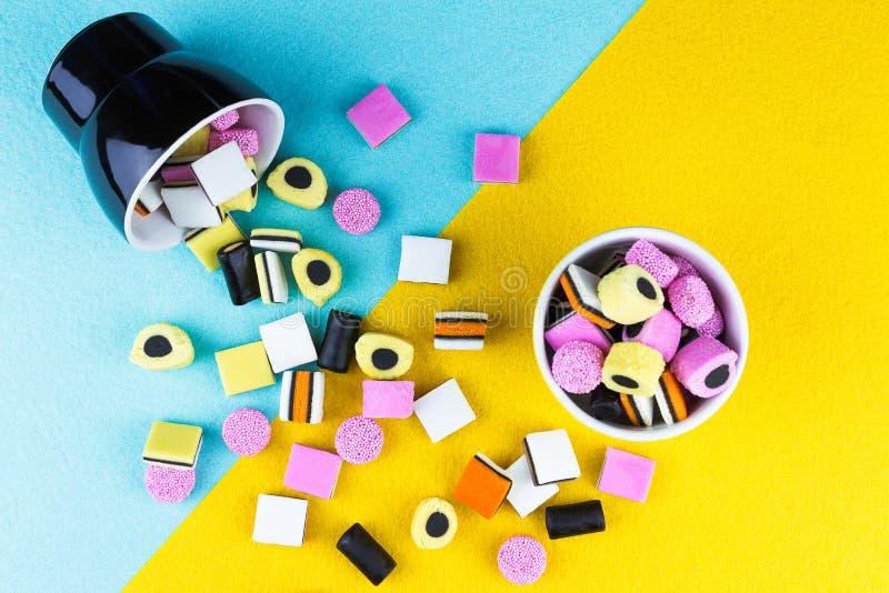 Regaliz colorido allsorts que desborda una taza fotografía de archivo