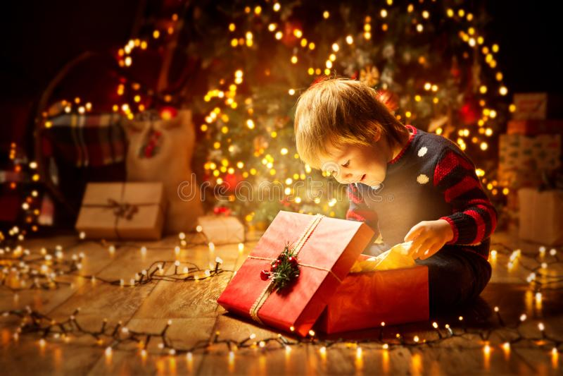 Regalo abierto del niño de la Navidad actual, bebé feliz que mira la caja fotografía de archivo