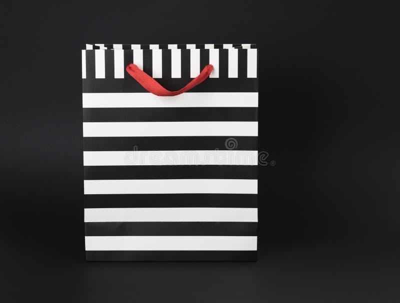 Regalo-bolso pelado blanco y negro con las manijas rojas del satén, en un fondo negro imágenes de archivo libres de regalías