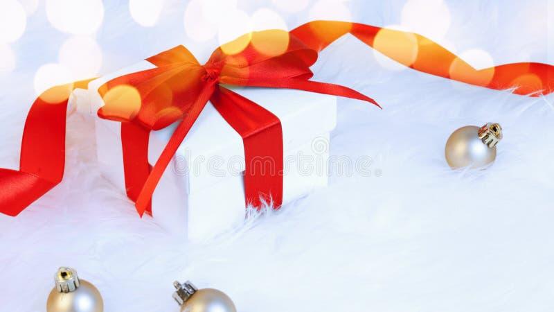 Regalo brillante di Natale con l'arco giallo delle palle su neve decorativa fotografia stock
