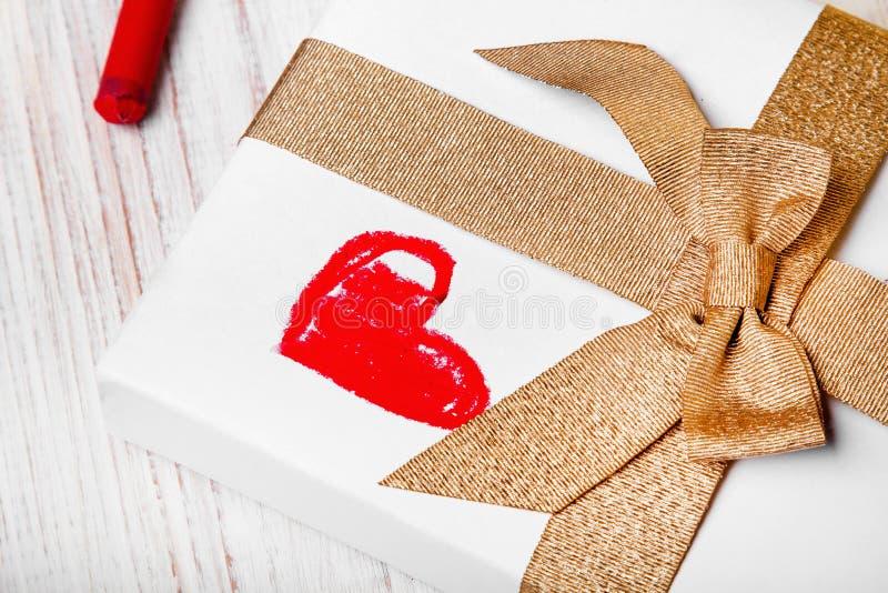 Regalo con la cinta del oro y el dibujo rojo del corazón imágenes de archivo libres de regalías