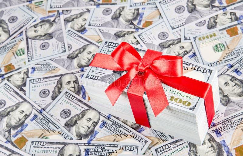 Regalo con la cinta roja grande del arco hecha de curr de los dólares de Estados Unidos imagen de archivo libre de regalías