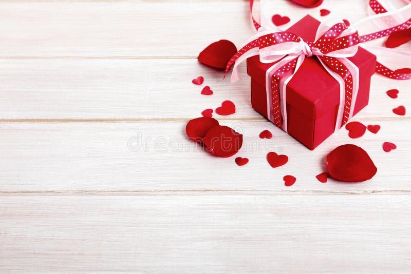 Regalo con los pétalos color de rosa, espacio de madera de la tarjeta del día de San Valentín de la copia foto de archivo