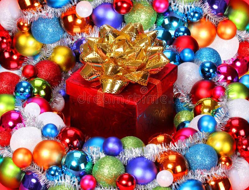 Regalo de la Navidad con el arco del oro y las bolas coloridas. fotografía de archivo libre de regalías