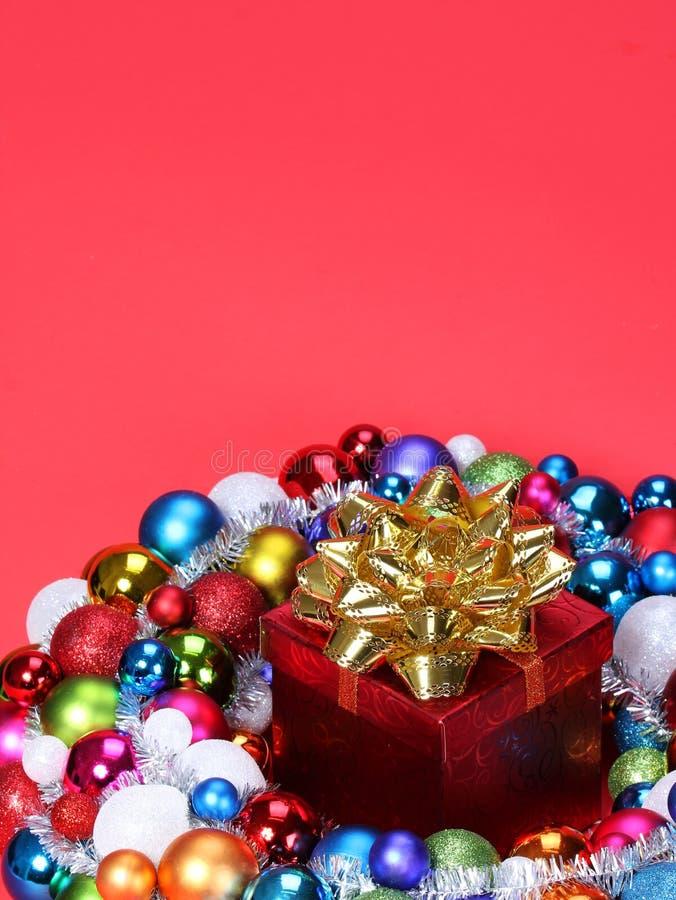 Regalo de la Navidad con el arco del oro y las bolas coloridas fotos de archivo