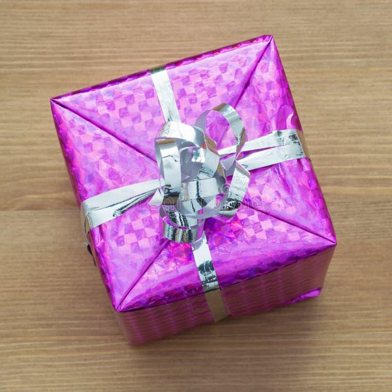 Regalo de la Navidad con la cinta envuelta en un papel púrpura brillante fotografía de archivo libre de regalías