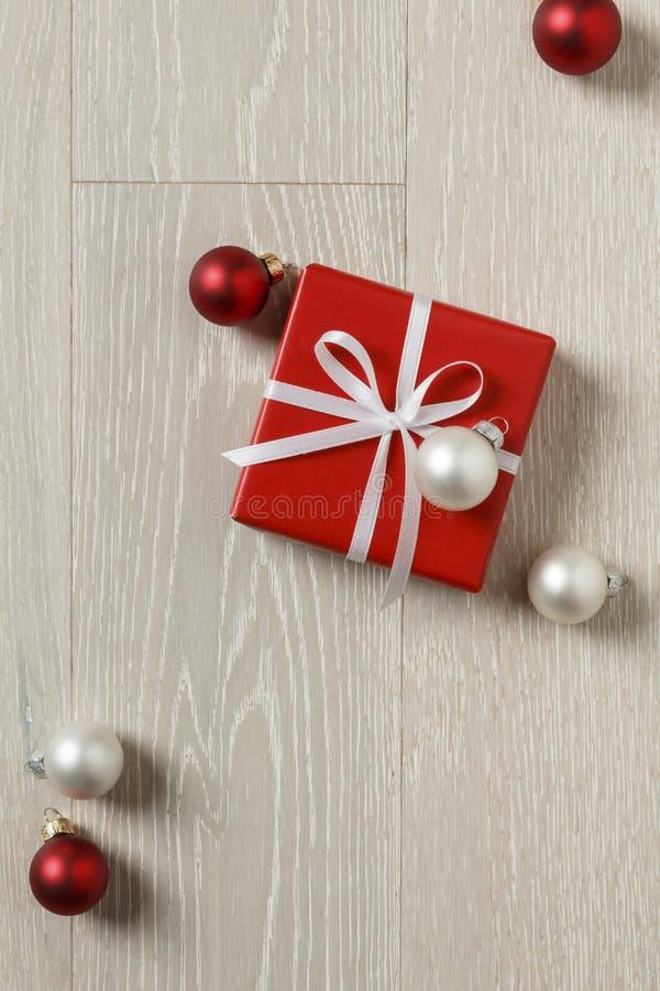 Regalo de la Navidad presente en fondo de madera rústico El rojo simple, clásico envolvió la caja de regalo con las decoraciones  imagen de archivo
