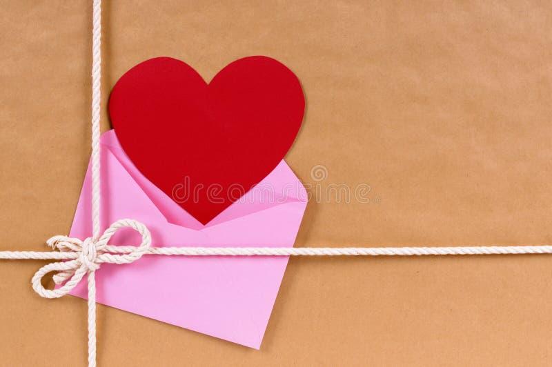 Regalo de la tarjeta del día de San Valentín, tarjeta roja o etiqueta del regalo, paquete del corazón del papel marrón imágenes de archivo libres de regalías
