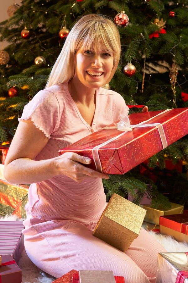 Regalo de Navidad de la apertura de la mujer delante del árbol fotos de archivo libres de regalías