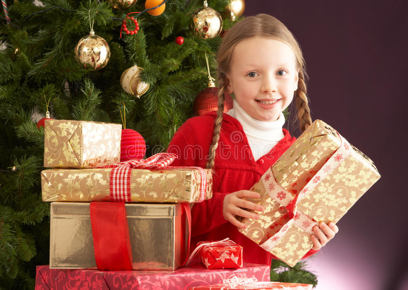 Regalo de Navidad de la explotación agrícola de la muchacha delante del árbol imagen de archivo libre de regalías