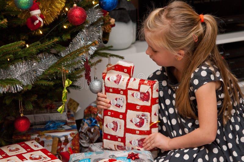 Regalo de Navidad de la abertura de la muchacha debajo del árbol de navidad imagenes de archivo