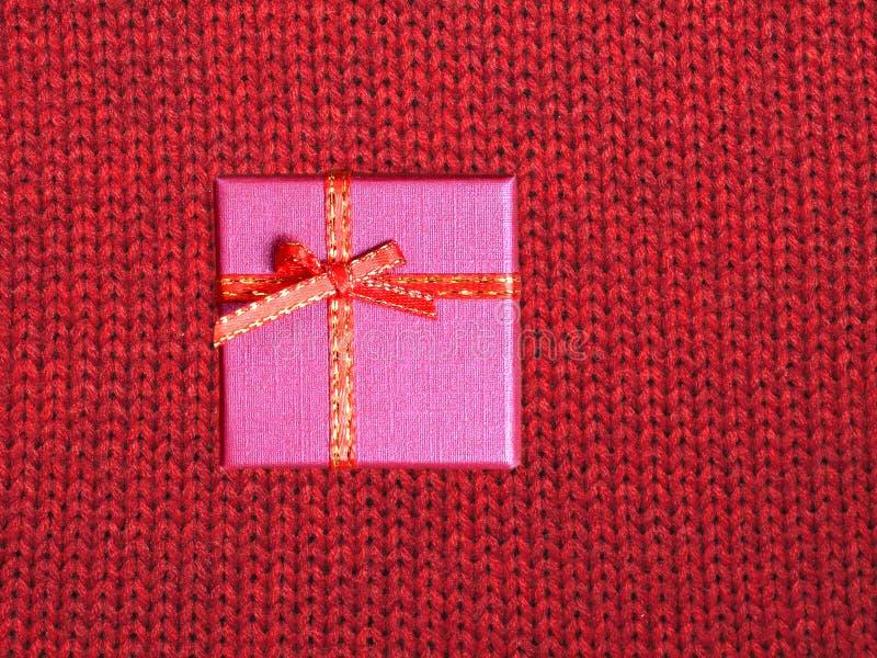 Regalo de vacaciones de la Navidad en la pequeña caja de color cubierta con la cinta con el arco contra fondo rojo de la opinión  fotografía de archivo