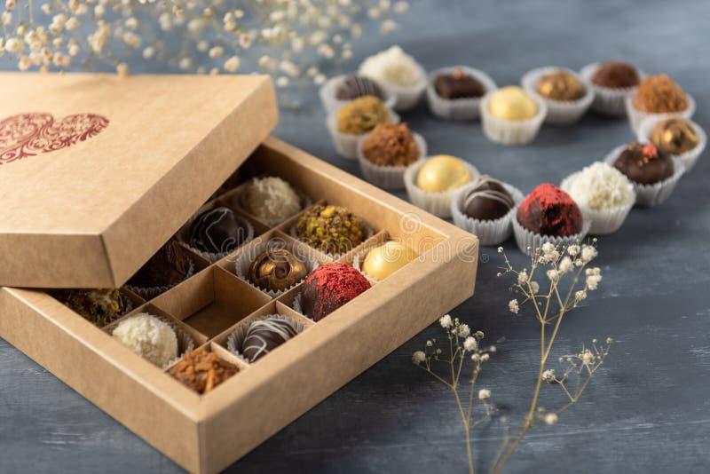 Regalo del cioccolato di San Valentino messo su fondo scuro Contenitore di caramella del mestiere con le caramelle a forma di del immagini stock libere da diritti