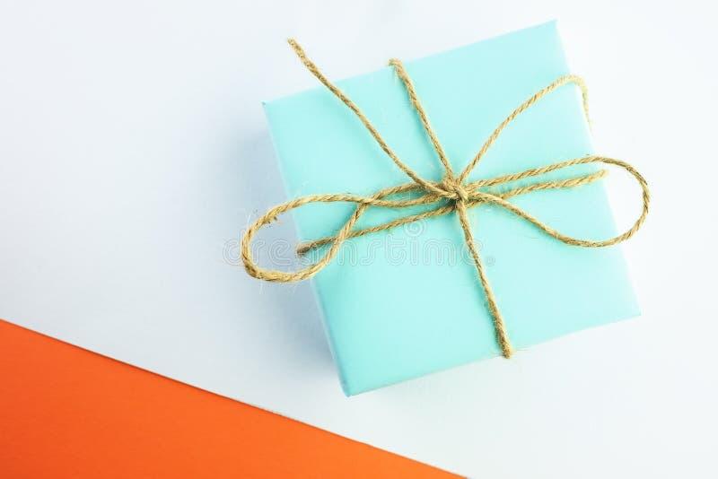 Regalo del color azul atado con guita en un fondo blanco-anaranjado foto de archivo