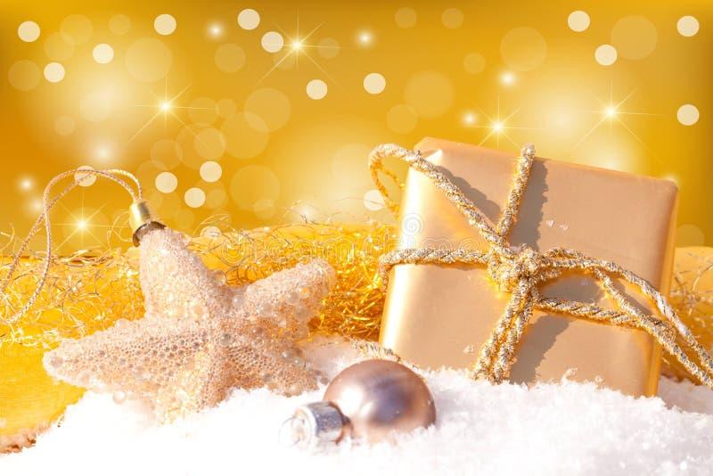 Regalo del oro con la bola de la Navidad imagenes de archivo