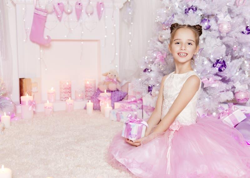 Regalo del presente della ragazza del bambino di Natale, bambino nella stanza rosa decorata immagini stock libere da diritti