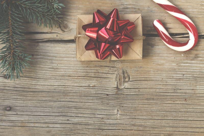 Regalo del ` s del Año Nuevo en una caja hecha en casa con un arco rojo cerca de los bastones spruce peludos de la rama y de cara foto de archivo libre de regalías
