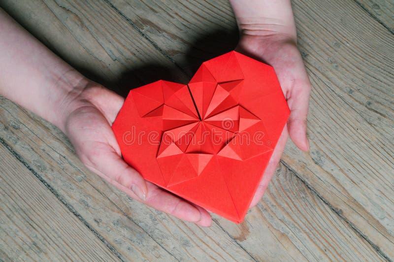 Regalo del ` s de la tarjeta del día de San Valentín, corazón en manos imagenes de archivo