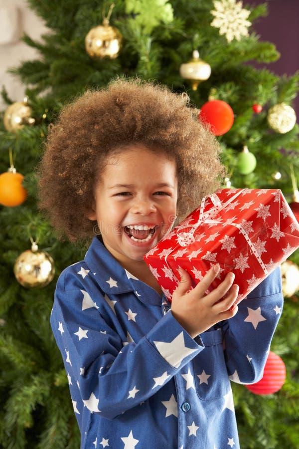 Regalo della holding del ragazzo davanti all'albero di Natale fotografia stock